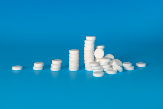 Drug use escalation, substance abuse or addiction concept. Pill stacks growing from left to right, ending with a pile of pills fallen over. White chalky tablets. Cyan or light blue background.