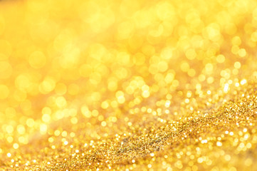 Gold glitter texture. Sparkling gold bright bokeh from blurred diamond dust. Abstract golden bokeh...