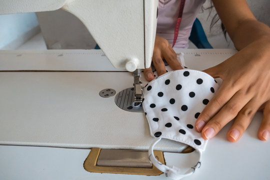 A close-up of the seamstress sitting and sewing face mask at home