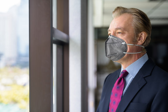 Mature businessman thinking and looking outside the window with mask for protection from corona virus outbreak