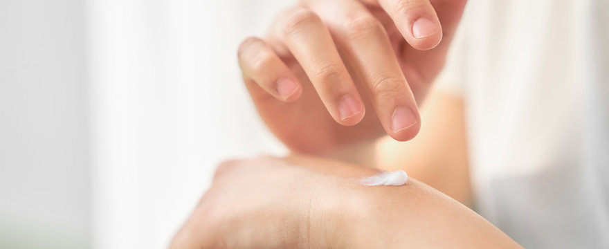 Close up of woman hand holding and applying moisturiser, Body lotion, isolated on white background.