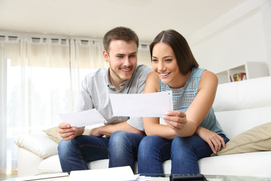 Happy couple looking and checking bills at home