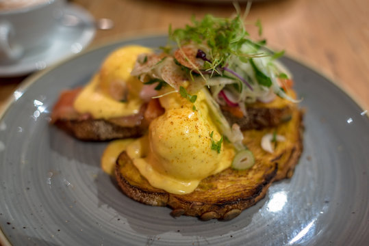 Eggs benedict on sourdough toast with greens, pesto and mushrooms
