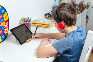 Eight years old boy behind the table study at home using a tablet and headphones, digital education, homeschooling at isolation