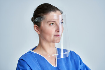 Wall Mural - Close up portrait of female medical doctor or nurse wearing face shield