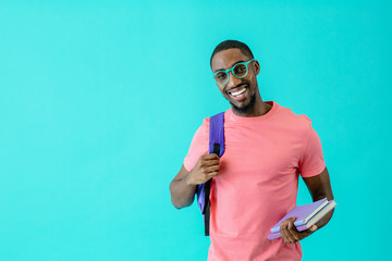 Portrait of a happy young man in pink shirt with glasses, books and school backpack looking at camera, isolated on blue