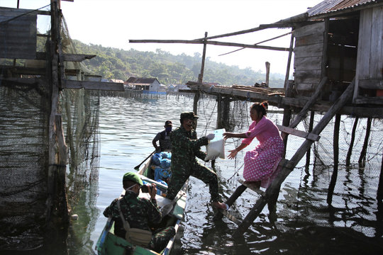 Indonesian soldiers use a boat to give free basic food for Bajo people amid the coronavirus disease (COVID-19) outbreak in Konawe