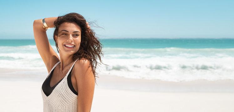 Happy fashion woman smiling at beach