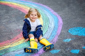 Happy little toddler girl in rubber boots with rainbow painted with colorful chalks on ground during pandemic coronavirus quarantine. Children painting rainbows along with the words Let's all be well Fotomurales