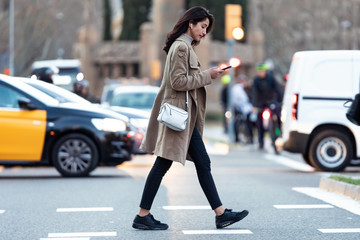 Pretty young woman crossing the street while listen to music with the wireless earphones.