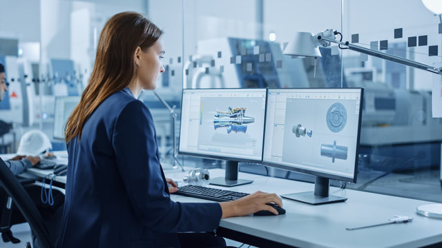 Portrait of Young and Confident Industrial Engineer Working on Computer, on Screen CAD Software Showing New Generation Electric Engine. Industrial Factory with High-Tech CNC Machinery.