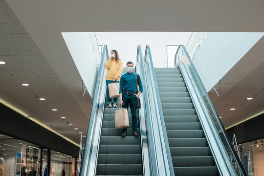 young man in a protective mask standing on an escalator in a shopping center