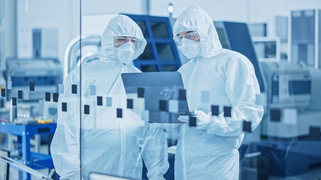 Modern Factory Sterile Workshop: Professionals in Coveralls, Masks Use Laptop and Talk. Medical Manufacturing Laboratory with High Tech CNC Machinery, Robot Arm Production Line and Automatic Equipment