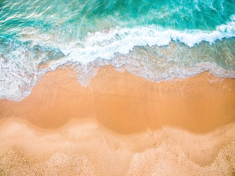 Aerial shot of beautiful sea waves and sandy ground in Ericeira beach, Portugal