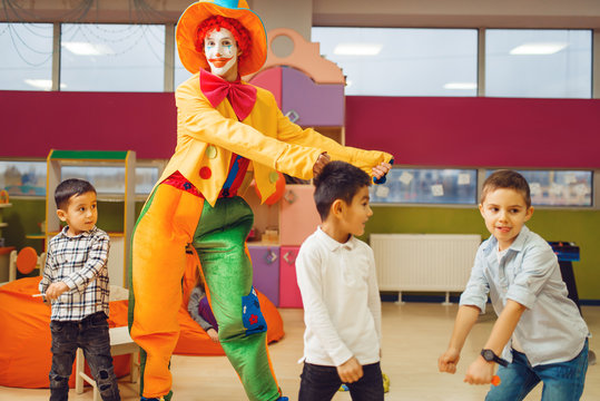 Funny clown animator dancing with little boys