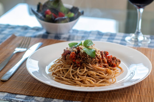 wholemeal spaghetti pasta with bolognese sauce and basil on a white plate