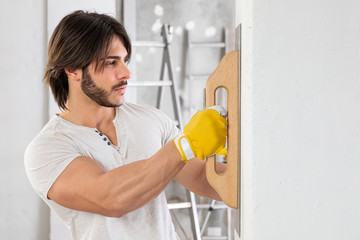 Plasterer finishing the surface of a white wall