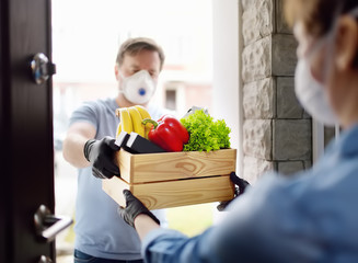 Courier or volunteer delivering shopping to woman during coronavirus quarantine. Woman customer receiving online order from courier at home. Express food delivery service on door. Papier Peint