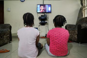 Kids watch an animation video created by Nigerian filmmaker, Niyi Akinmolayan to educate kids on coronavirus, in their home, amid the spread of coronavirus disease (COVID-19), in Lagos