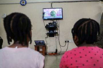 Kids watch an animation video created by Nigerian filmmaker, Niyi Akinmolayan to educate kids on coronavirus, in their home, amid the spread of the coronavirus disease (COVID-19), in Lagos
