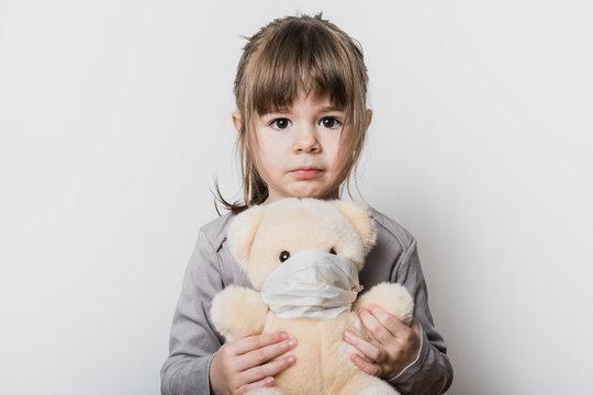 Uen petite fille tenant son ours en peluche avec un masque pendant la période du confinement du coronavirus