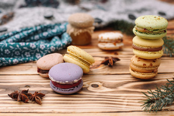 Homemade colorful macaroons are lying on the brown wooden table. Cup of coffee. Anise, honey and colorful tissue.