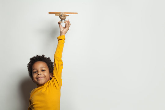 Little black child boy with plane model on white background