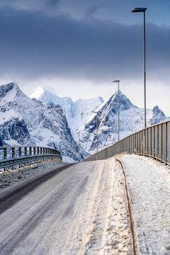 Bridge against snowcapped mountains in Reine, Norway