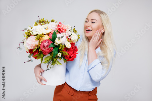 valentine's day or mother's day concept - portrait of surprised beautiful and elegant plus size blonde woman holding box with summer flowers over gray