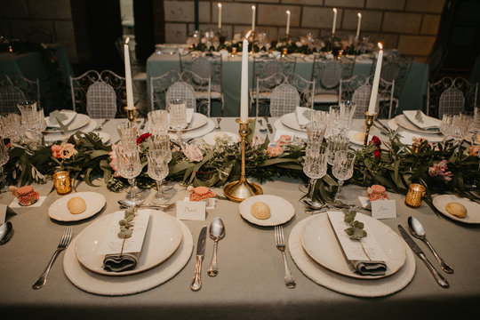 Candles and flowers placed near tableware old long table during wedding banquet in spacious room at night