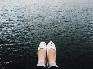 Low Section Of Woman Legs Against Lake Wall mural
