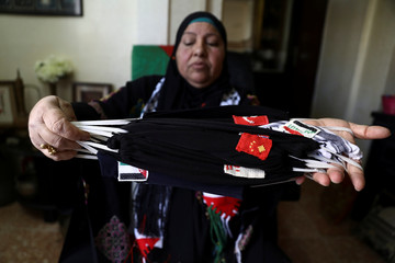 Fatima Khader, a Palestinian woman from east Jerusalem, stitches masks with flags of various countries onto fabric, amid the coronavirus disease (COVID-19) spread