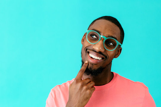 Portrait of a happy young man with glasses smiling, thinking and looking up with finger on chin, against blue studio background