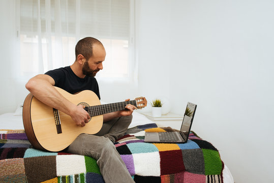 Man sitting on bed taking an online guitar lessons during Coronavirus confinement.