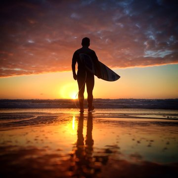 Silhouette Man Carrying Surfboard On Beach At Sunset