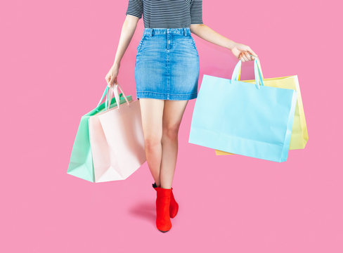 The woman low body part wore Denim skirt and red boots. Carrying a shopping bag in many pastel colors on pink background selective focus with copy space