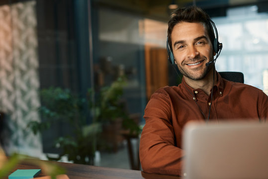 Smiling businessman talking on a headset in his office