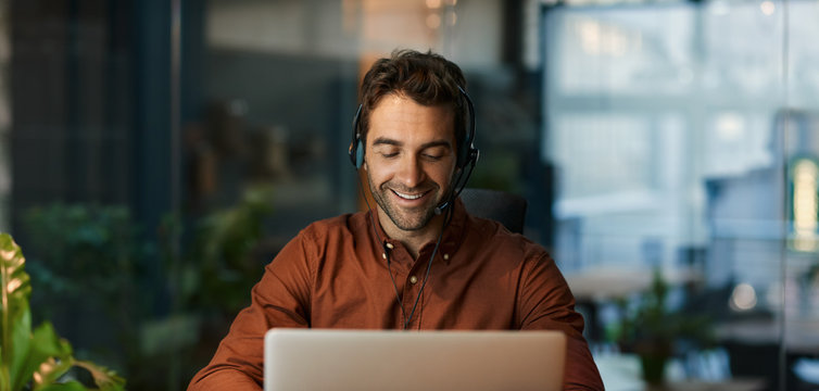 Smiling businessman talking on a headset and using a laptop