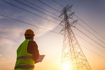Fototapeta Asian Manager Engineering in standard safety uniform working inspect the electricity high voltage pole. obraz