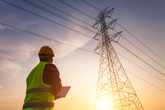 Asian Manager Engineering in standard safety uniform working inspect the electricity high voltage pole.