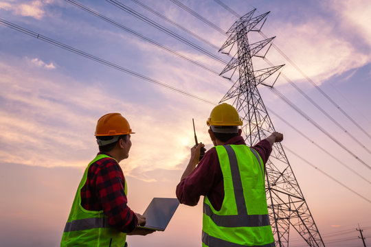 Asian Manager Engineering and worker in standard safety uniform working inspect the electricity high voltage pole.