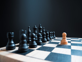 A single white chess pawn piece standing alone on a chessboard against a full team. Conceptual photo of an impossible fight and overcoming life's difficulties alone. Self-motivation.