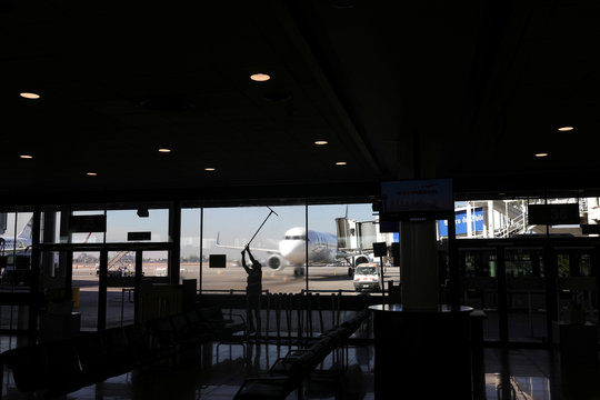 A worker cleans a window at Santiago's airport during a preventive quarantine after the outbreak of the coronavirus disease (COVID-19), in Santiago