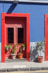 Red picturesque door on a blue wall in medieval La Laguna town are decorated with flowers, Tenerife, Canary Islands, Spain.