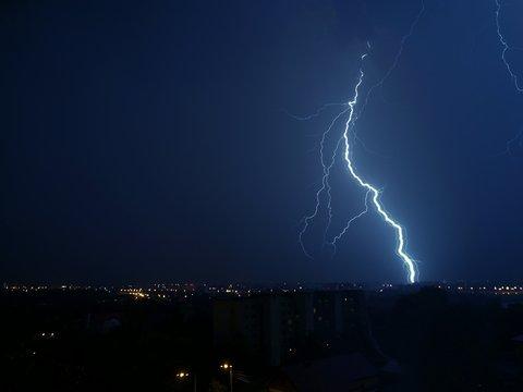 Lightening Over Illuminated City At Night
