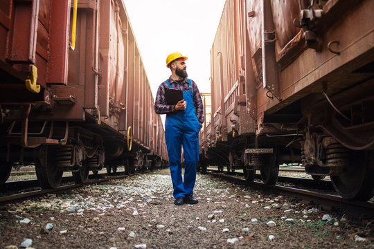 Railway transportation supervisor checking trains and cargo. Checking on freight train cars and shipping containers. Organizing goods export and expecting delivery.