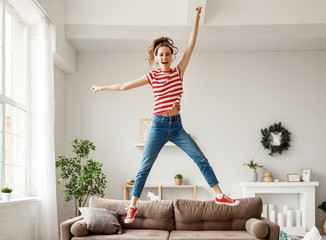 Spoed Fotobehang Dance School Happy woman listening to music and jumping and dancing on couch at home.