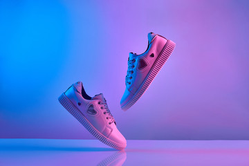 Trendy white teenage sneakers flying in trendy neon light. Levitation Shoes in red, blue light....