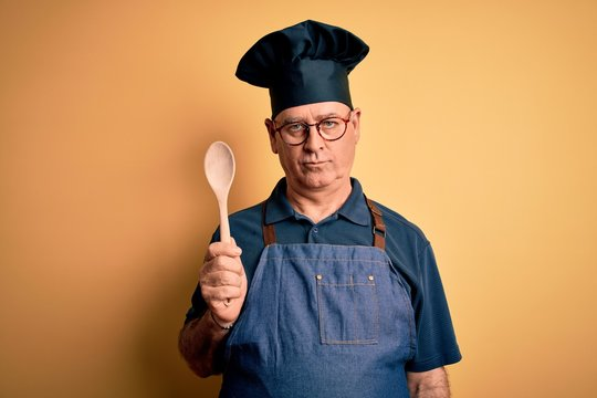 Middle age cooker man wearing apron and hat holding wooden spoon over yellow background with a confident expression on smart face thinking serious