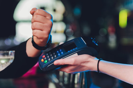 close up hand of young customer male paying with credit transaction by smart watch contactless terminal in modern shop, NFC technology.